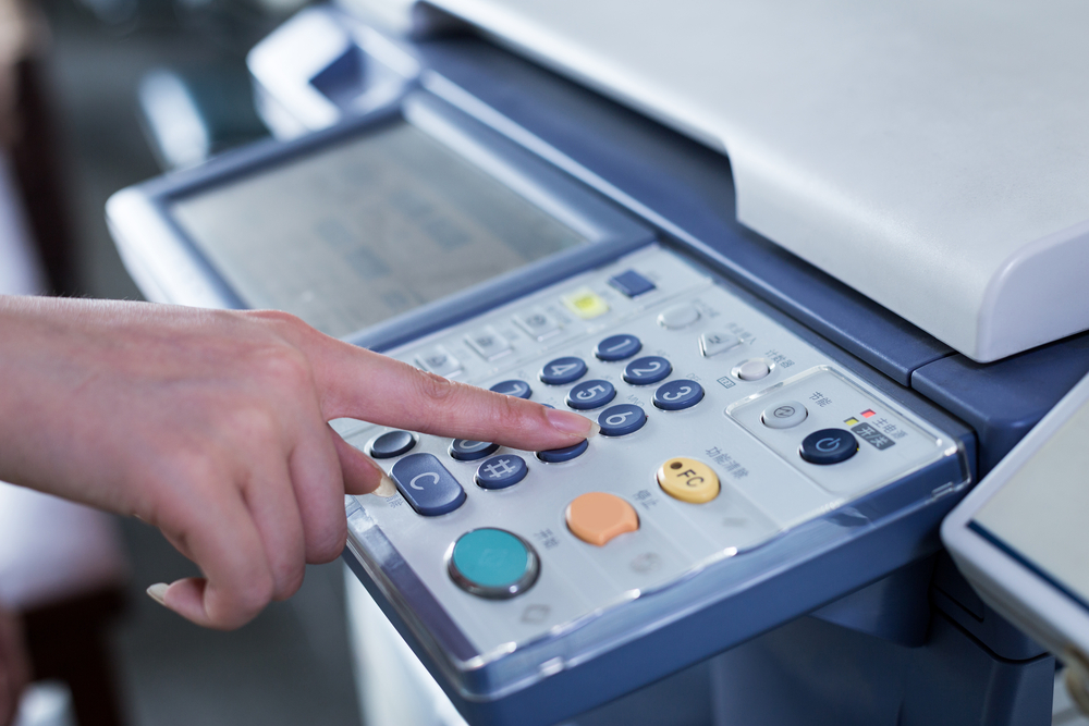 Close up of woman pressing button on multifunction printer and copier