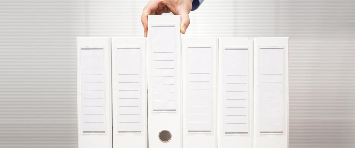 Man selecting binder of documents in toronto