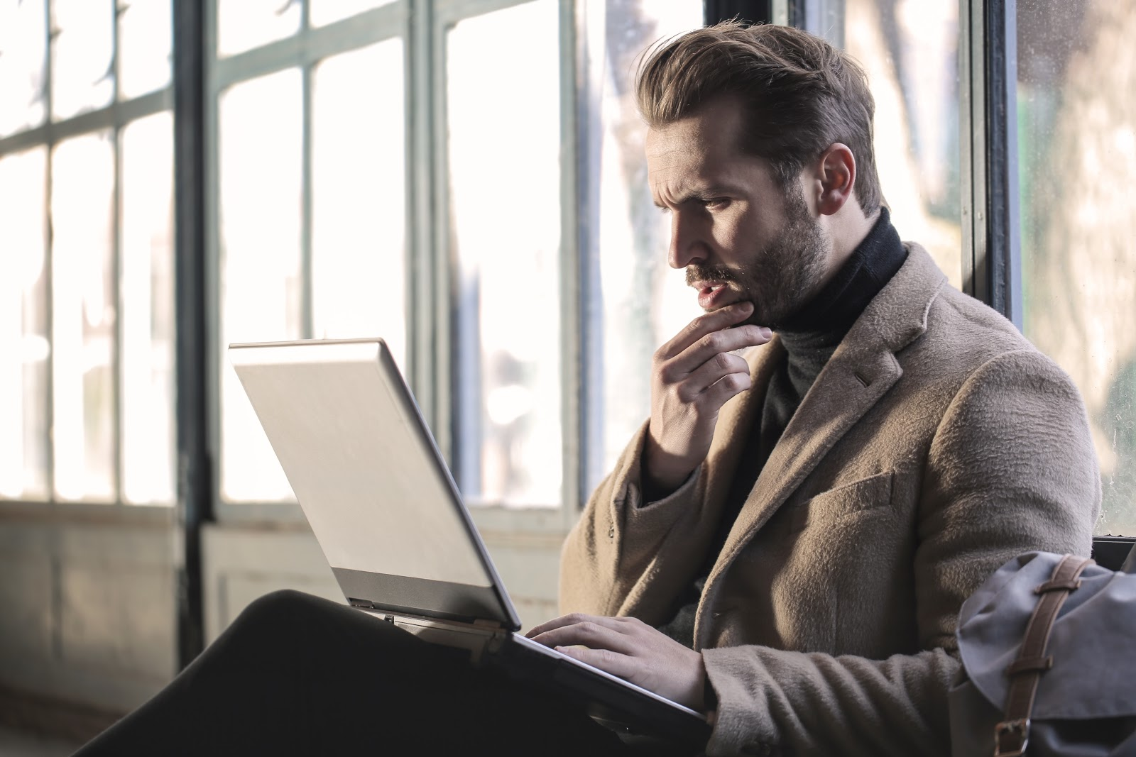 A man scratching his chin and looking at a laptop in confusion.