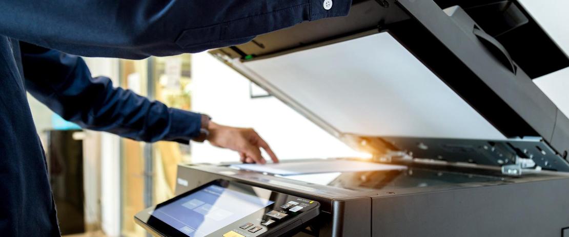 Close up of a man using a business printer rental