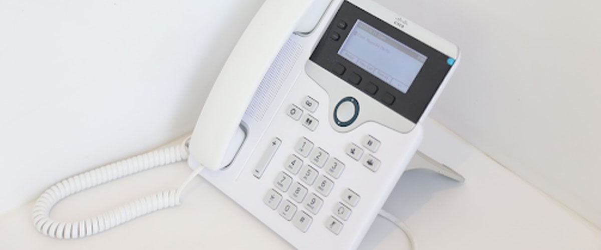 White phone on a white desk and background.