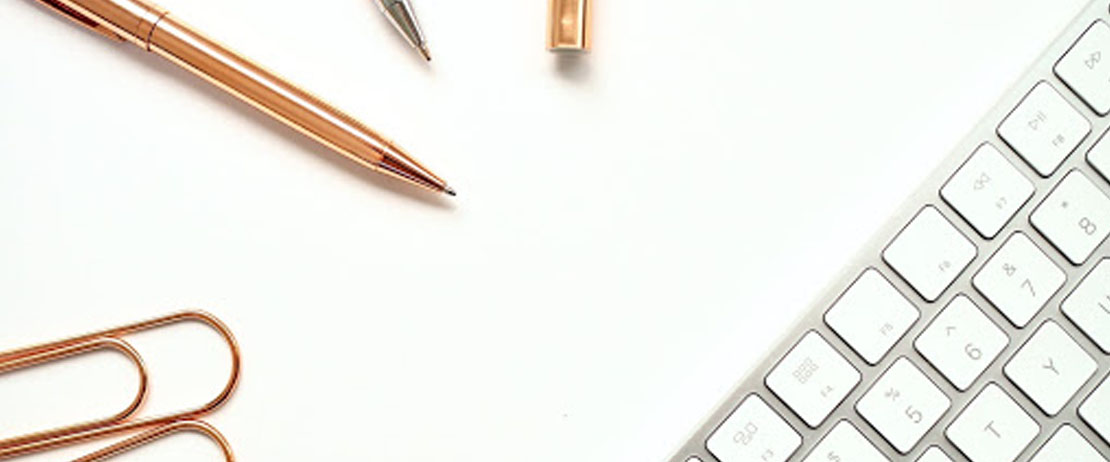 A keyboard, paperclips, and pens on a desk