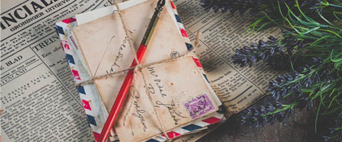 Envelopes and a fountain pen bound together with twine with a newspaper in the background