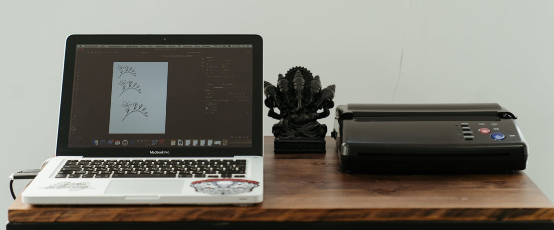 A laptop connected to a printer with a figurine in between