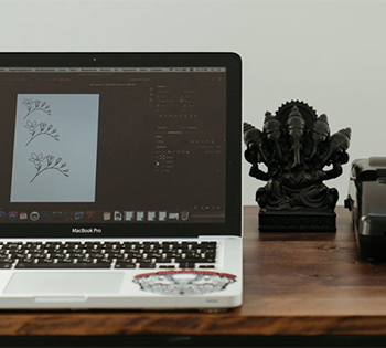 A printer, laptop, and figurine on a br