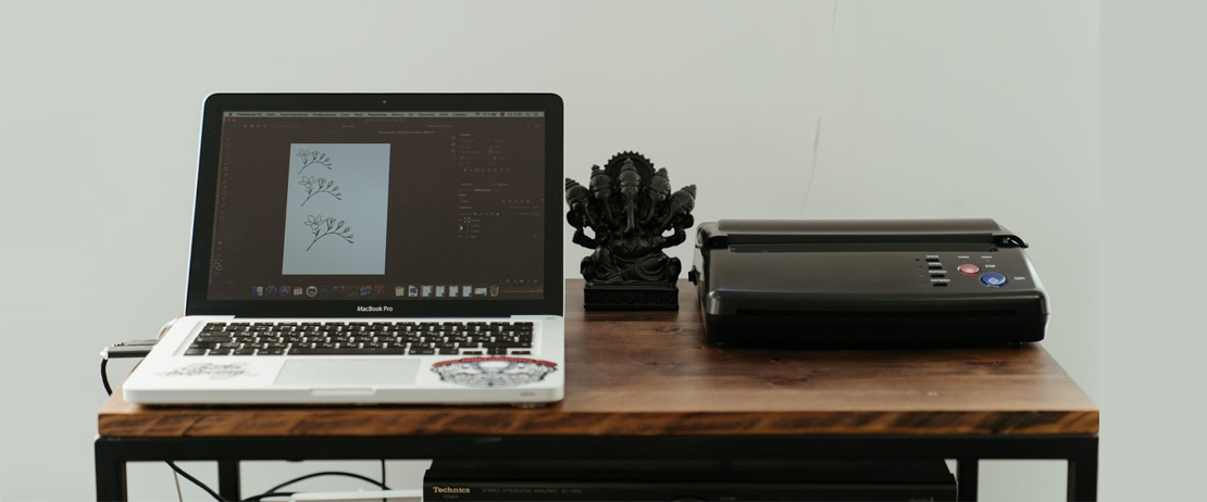 A printer, laptop, and figurine on a brown wooden table