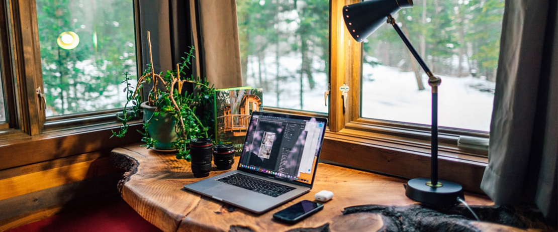 A laptop, cellphone, plant, and lamp on a wooden table by a window
