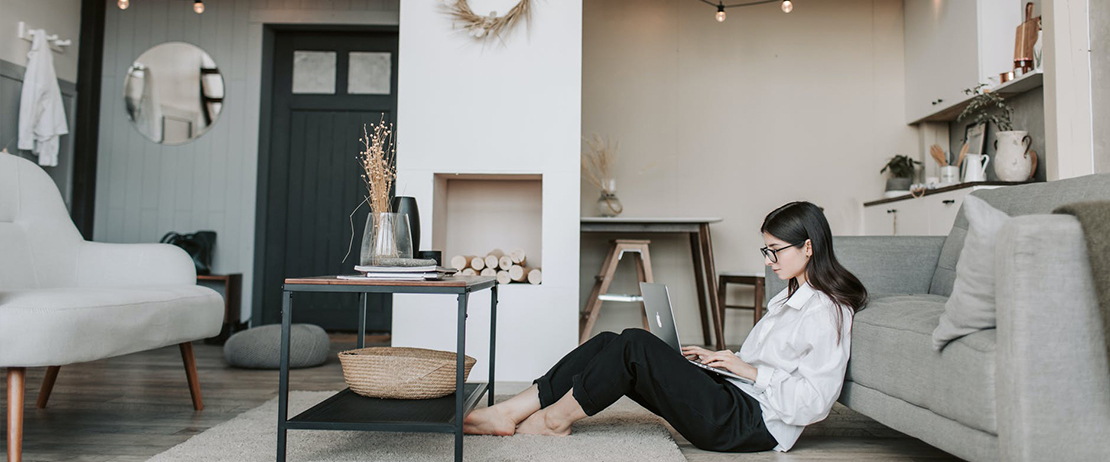 A woman sitting on the floor in a living room with a laptop on her lap
