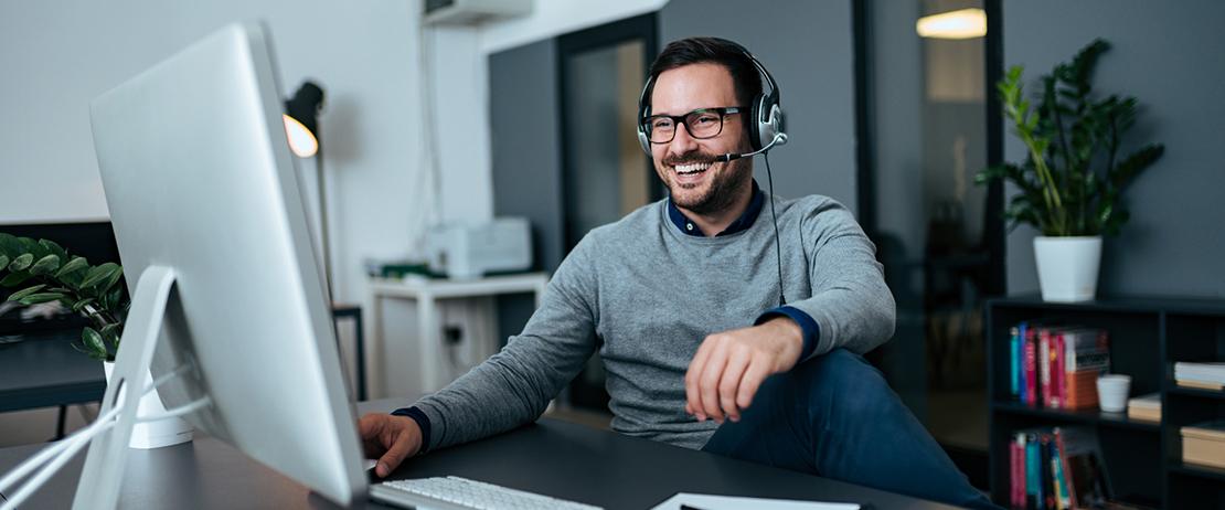 A man uses headphones during a virtual meeting