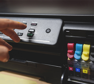 A black printer with CMYK ink cartridges