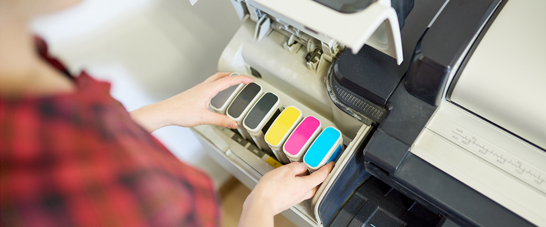 Someone checking the ink cartridges of a printer