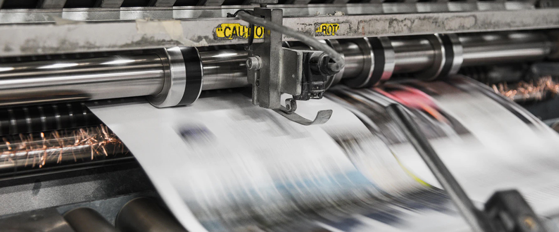 An industrial printer printing pages