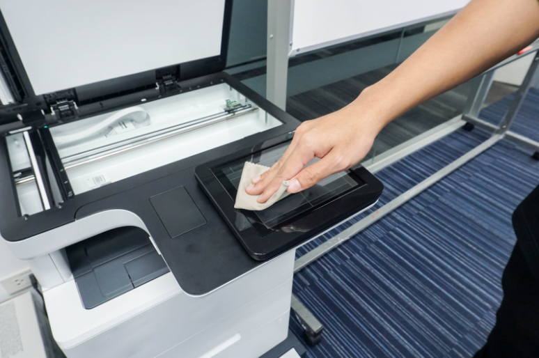 An employee wipes clean a company printer