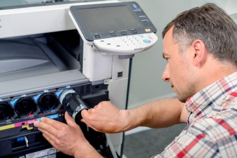 A man changing a printer's ink cartridges