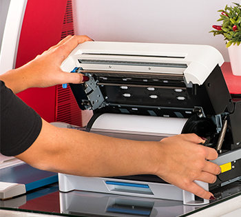 An individual operating a thermal transfer printer