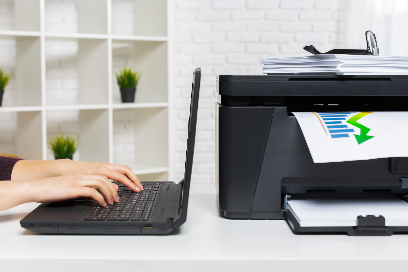 An individual uses a laptop to print from their home office