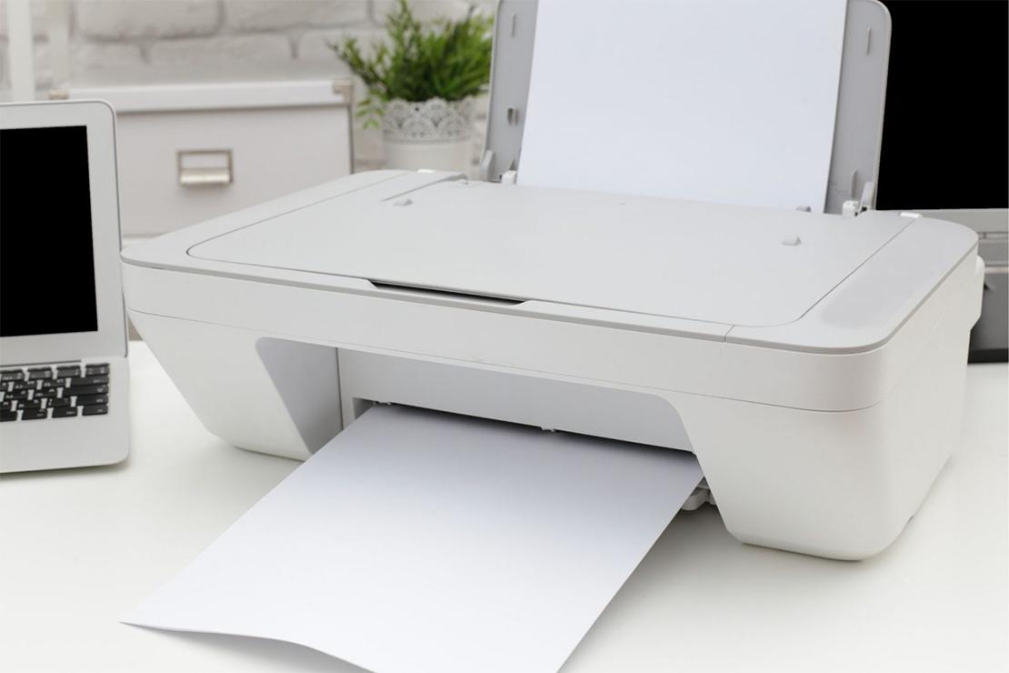A white printer on a desk next to a laptop