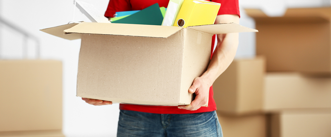 A person carrying a box of used office supplies