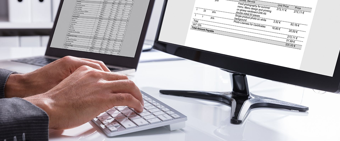 A person creating an invoice on a desktop computer
