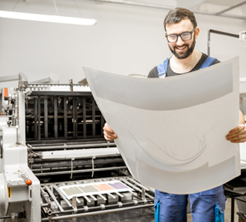 A man smiling at his printed work